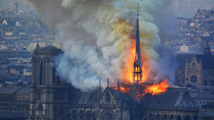 Smoke and flames rise during a fire at the landmark Notre-Dame Cathedral in central Paris on April 15, 2019, potentially involving renovation works being carried out at the site, the fire service said. - A major fire broke out at the landmark Notre-Dame Cathedral in central Paris sending flames and huge clouds of grey smoke billowing into the sky, the fire service said. The flames and smoke plumed from the spire and roof of the gothic cathedral, visited by millions of people a year, where renovations are currently underway. (Photo by Hubert Hitier / AFP)