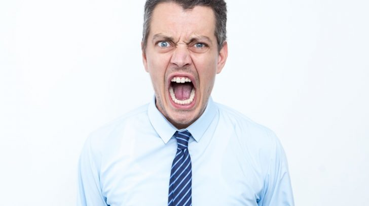Closeup portrait of furious middle-aged business man looking at camera and screaming. Isolated view on white background.