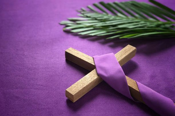 A religious cross and palm leaves on purple background.