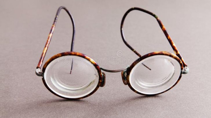 lentes-viejas-de-las-gafas-del-diseño-la-moda-en-fondo-papel-gris-complementos-los-hombres-estilo-vintage-visión-macra-102423310